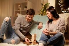Glückliches Paar, das zu Hause Block-stapelndes Spiel spielt Lizenzfreie Stockbilder
