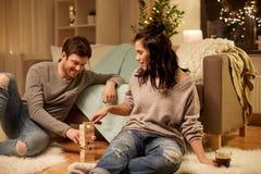 Glückliches Paar, das zu Hause Block-stapelndes Spiel spielt Lizenzfreies Stockfoto