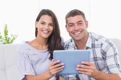 Glückliches Paar, das zu Hause digitale Tablette hält Stockbild