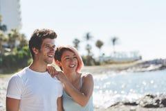 Glückliches Paar, das zusammen auf dem Strand weg schaut steht stockfotos