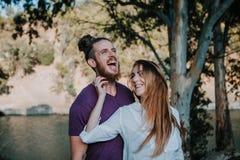 Glückliches Paar, das zusammen in der Natur genießt und lacht Lizenzfreie Stockfotos