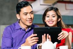 Glückliches Paar, das zusammen ein lustiges on-line-Video auf einer Tablette aufpasst stockfoto