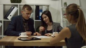 Glückliches Paar, das zusammen einen Vertrag im Büro unterzeichnet stock video