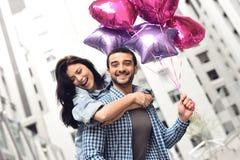 Glückliches Paar in der Gasse mit Geburtstagsballonen Stockfotos