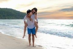 Glückliches Paar in der Liebe auf Strandsommerferien Frohes Mädchen, das auf dem jungen Freund hat Spaß huckepack trägt stockfotos