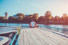 Glückliches Paar in der Liebe, die auf dem Flussdock bei Sonnenuntergang umarmt Junge Leute, die durch das Wasser kühlen Stockfotografie