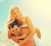 Glückliches Paar in der Liebe, die auf dem Strand umarmt und lacht Lizenzfreies Stockbild