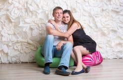 Glückliches Paar in der Liebe, die auf Sitzsäcken am Studio sitzt Stockfoto