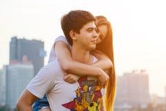 Glückliches Paar in der Liebe, die den Spaß draußen umarmt das küssende und lächelnde Piggybanking hat Stockbilder