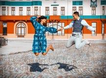 Glückliches Paar in der Liebe, die hoch in einer Luft in der Mitte der Straße springt lizenzfreie stockfotos