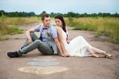 Glückliches Paar in der Liebe, die Spaß auf dem Gebiet voll von Sonnenblumen hat Stockfotografie