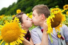 Glückliches Paar in der Liebe, die Spaß auf dem Gebiet voll von Sonnenblumen hat Lizenzfreie Stockfotos