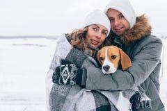 Glückliches Paar an der Winterlandschaftsglücklichen Familie mit Spürhundhund Stunden und Landschaft lizenzfreies stockfoto