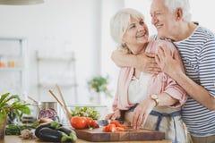Glückliches Paar des strengen Vegetariers macht das Mittagessen lizenzfreie stockbilder