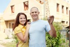 Glückliches Paar gegen das Bauen des neuen Hauses Stockfoto
