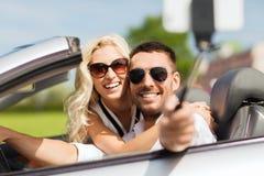 Glückliches Paar im Auto, das selfie mit Smartphone nimmt Stockbild