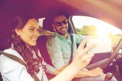 Glückliches Paar im Auto, das selfie mit Smartphone nimmt lizenzfreie stockbilder