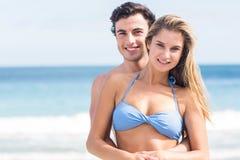 Glückliches Paar im Badeanzug, der Kamera und die Umfassung betrachtet Stockfotografie