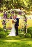 Glückliches Paar im Blumenbogen Stockfotos