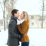Glückliches Paar im Freien in der Liebe, die im kalten Winterwetter aufwirft Stockbild