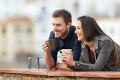 Glückliches Paar im Urlaub, das weg schauen trinkt stockbild