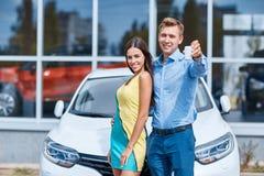 Glückliches Paar kaufte einen Neuwagen und zeigt die Schlüssel zu ihm lizenzfreie stockfotos