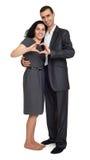 Glückliches Paar kleidete im starken klassischen Kleid an und machte Herzform von den Fingern, Studioporträt auf Weiß Stockfotografie