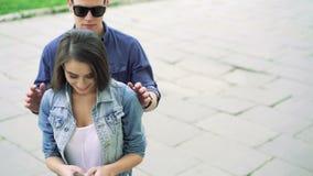 Glückliches Paar: lostening Musik des Mädchens auf Telefon, dem Jungen, der zu ihr kommen und dem Lächeln 4K stock video