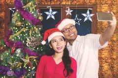 Glückliches Paar macht Foto mit Weihnachtsbaum Stockfoto
