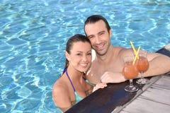 Glückliches Paar mit Cocktails durch das Pool Lizenzfreies Stockfoto