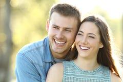 Glückliches Paar mit dem perfekten Lächeln, das Seite betrachtet lizenzfreies stockbild