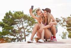 Glückliches Paar mit dem Sitzen auf Skateboard und dem Nehmen eines selfie Stockfotos