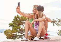 Glückliches Paar mit dem Sitzen auf Skateboard und dem Nehmen eines selfie Lizenzfreie Stockbilder