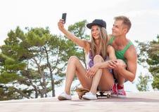 Glückliches Paar mit dem Sitzen auf Skateboard und dem Nehmen eines selfie Lizenzfreie Stockfotos