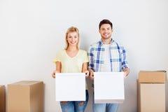 Glückliches Paar mit den Kästen, die auf neues Haus sich bewegen stockfotografie