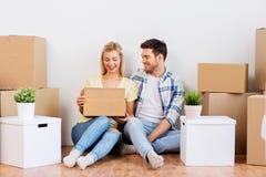 Glückliches Paar mit den Kästen, die auf neues Haus sich bewegen lizenzfreie stockbilder