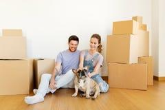 Glückliches Paar mit den Kästen und Hund, die auf neues Haus sich bewegen Stockbilder