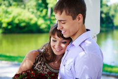 Glückliches Paar mit einem Blumenstrauß der roten Rosen in einem Sommerpark Lizenzfreies Stockbild