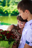 Glückliches Paar mit einem Blumenstrauß der roten Rosen umarmt in einem Sommerpark Stockbilder