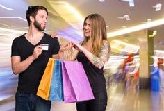 Glückliches Paar mit Einkaufstaschen im mal Stockfotos