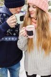 Glückliches Paar mit heißen Getränken in den Schalen im Wald Stockfotografie