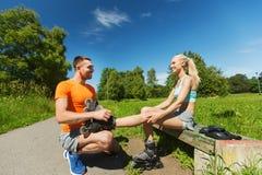 Glückliches Paar mit Rollerblades draußen Stockfotografie