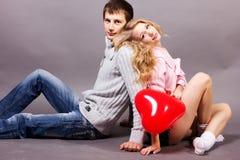 Glückliches Paar mit rotem Ballon. Valentinsgrußtag Lizenzfreies Stockfoto
