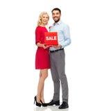 Glückliches Paar mit rotem Verkaufszeichen Stockbild