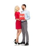 Glückliches Paar mit rotem Verkaufszeichen Stockfoto