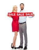 Glückliches Paar mit rotem Verkaufszeichen Stockfotos