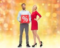 Glückliches Paar mit rotem Verkaufszeichen Stockbilder