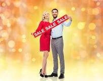 Glückliches Paar mit rotem Verkaufszeichen Lizenzfreies Stockbild