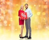 Glückliches Paar mit rotem Verkaufszeichen Lizenzfreie Stockfotografie