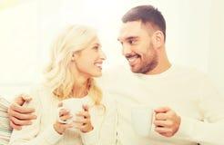 Glückliches Paar mit Schalen Tee zu Hause trinkend Stockfoto